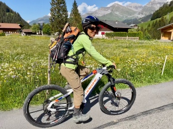A hiker on the E-mountain bike with full hiking gear